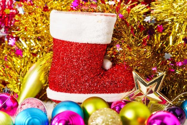 赤いサンタクロースのブーツとクリスマスの飾りの装飾の背景