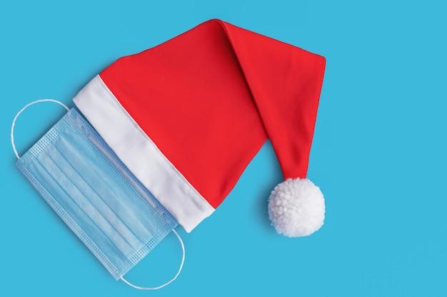 빨간 산타 클로스 모자와 의료 마스크