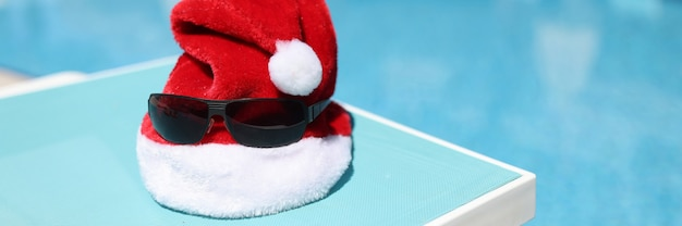 Red santa claus hat and sunglasses lying on sun lounger on shore of swimming pool closeup