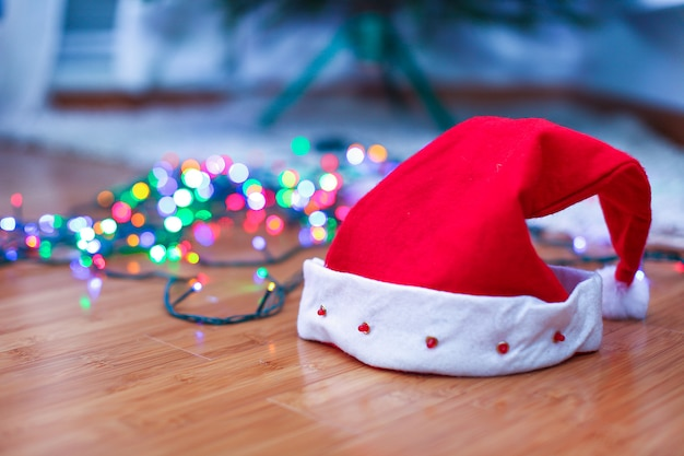 Red santa claus hat on a timber floor with brightly colored garlands, in lights background.