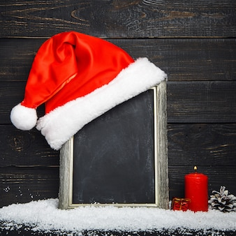 Red santa hat on the blackboard with snow