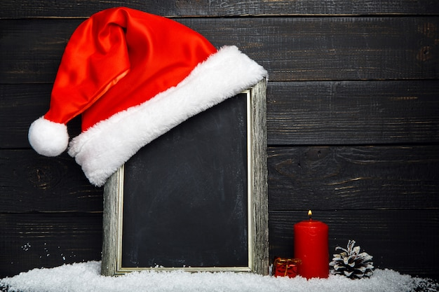 Red santa hat on the chalkboard with snow