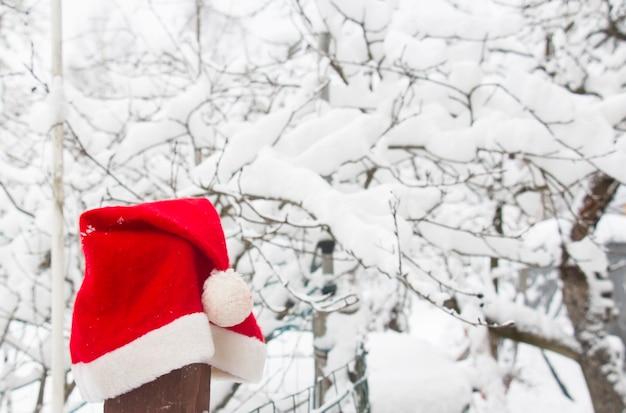 Красная шапка санта-клауса на заборе зимой в снежном лесу зимой