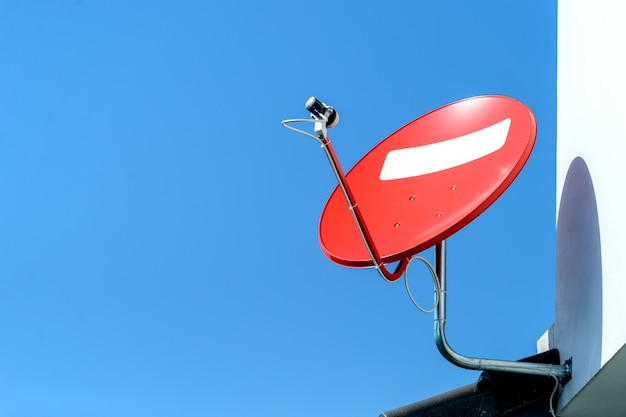 Red satellite dish with blue sky with soft-focus and over light in the background