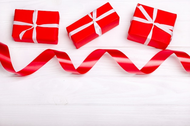 Red satin ribbon and box isolated on white background