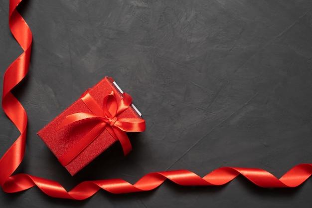구체적인 배경에 빨간색 새틴 리본입니다. 활과 상자. 2 월 14 일 사랑하는 사람을위한 선물 컨셉. baner. 복사 공간