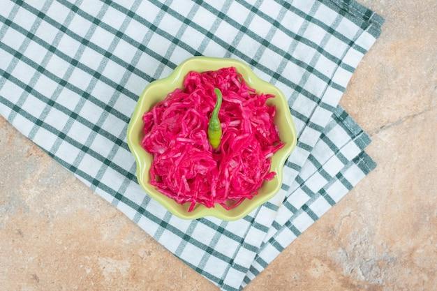 テーブルクロスと緑のボウルに赤いザワークラウトサラダ