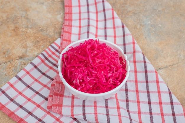 テーブルクロスと白いボウルに赤いザワークラウトサラダ