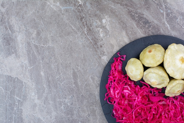 Red sauerkraut and vegetables on dark board.
