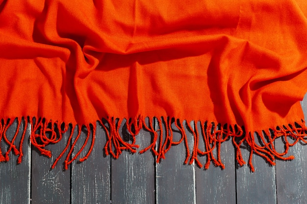 Red scarf over black wood table