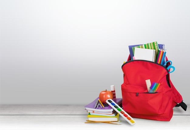 Красный школьный рюкзак на фоне.