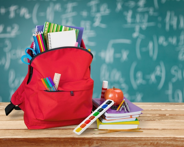 Red school backpack with colorful stationary