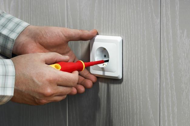 벽에 전기 콘센트에 손에 전기 기술자를위한 빨간색 드라이버