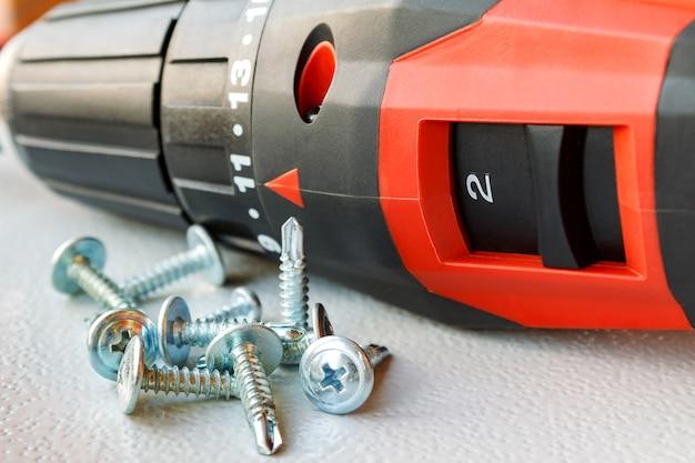Red screwdriver and screws for metal closeup