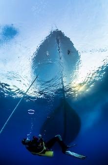 Красное море, африка, октябрь 2015: вид со дна моря на яхте на якоре. аквалангист на поверхности воды. морская жизнь под водой в голубом океане. наблюдение за животным миром. подводное плавание с аквалангом