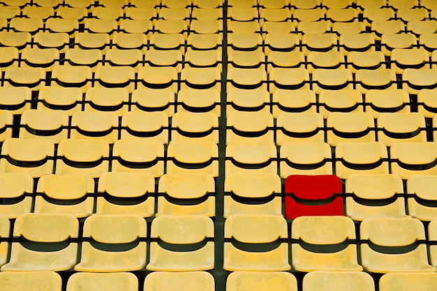Red seat in yellow seat pattern in football stadium