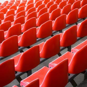 Красные сиденья на стадионе. пустое место футбольного стадиона.