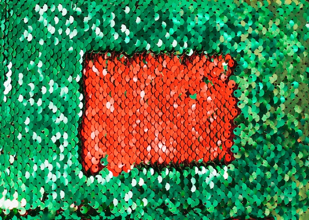 Red sequins inside the dark glitter green reflective sequins
