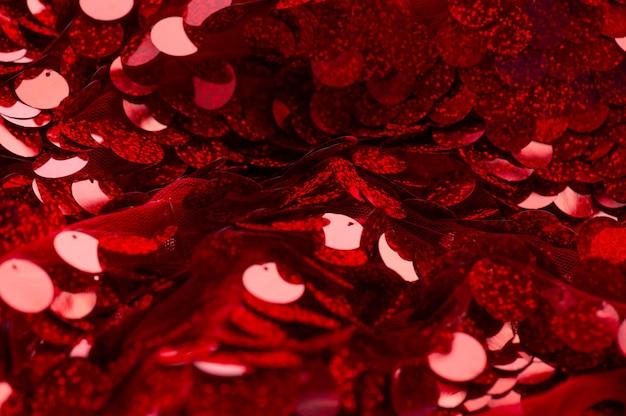 Красный узор блестки. сверкающий фон блестки. ткань с красными пайетками. прямоугольная красная блестящая ткань