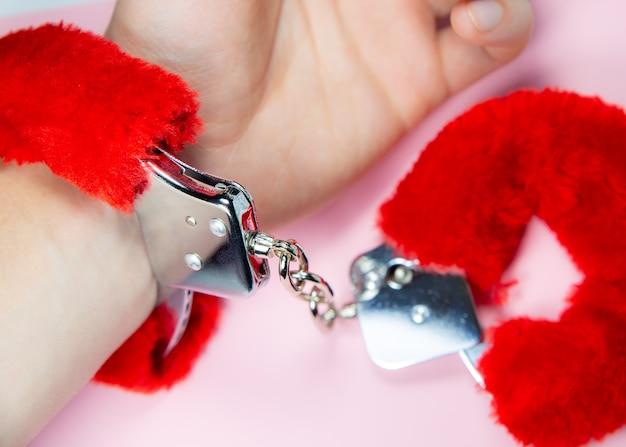 Красные сексуальные пушистые наручники на мужской руке.