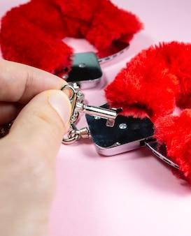 Красные сексуальные пушистые наручники с ключами на розовом фоне.