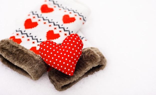 Красная форма сердца и варежки на снегу