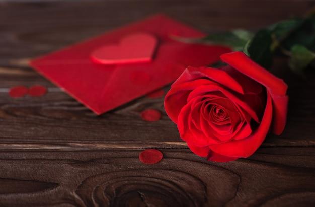 Красная форма сердца и красная роза на деревянном коричневом фоне