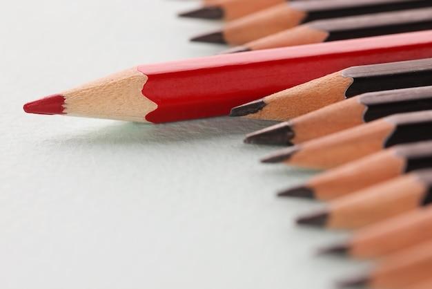 Красный острый деревянный карандаш, лежащий за черным фоном крупным планом