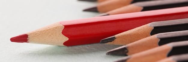 Red sharp wooden pencil lying beyond black closeup background