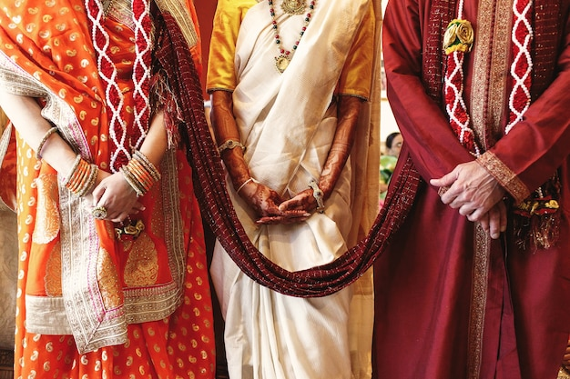Red shawl connects bride's parents dressed for indian wedding