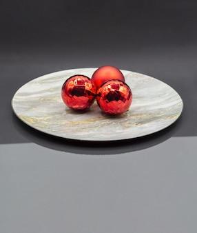 大理石のパターンプレート上の赤い光沢のあるクリスマスボール