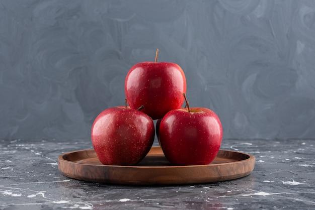 Красные блестящие целые яблоки на деревянной тарелке.