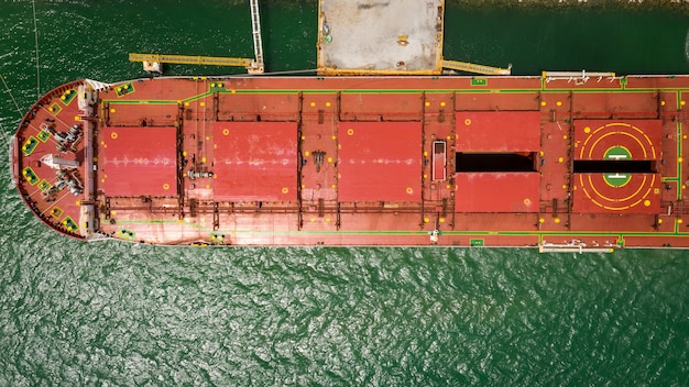 Red shipping repair in floating dock aerial view