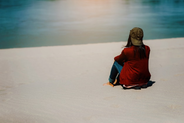 A red shirt woman sitting on a sandy beach facing the river or the sea.