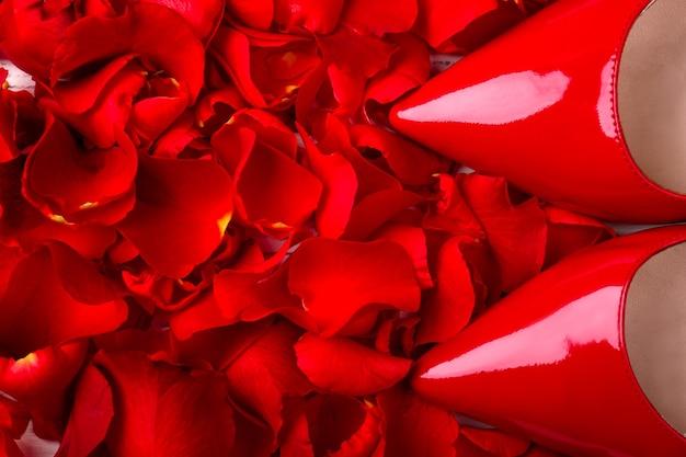 情熱の光沢のある色の赤い靴とバラの花びらの靴