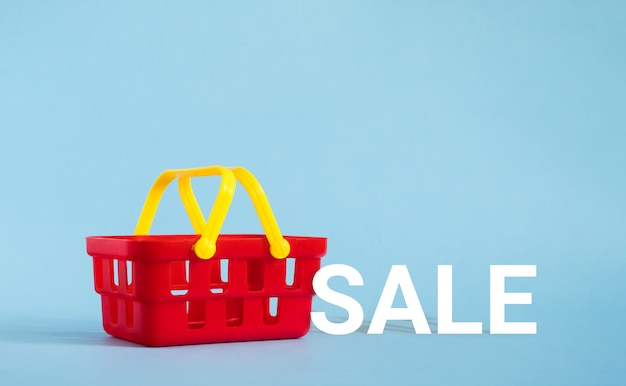 Red shopping basket on blue background. sale and shopping concept. copy space