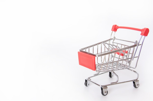 Red shopping cart or empty supermarket cart isolated on white background with copy space