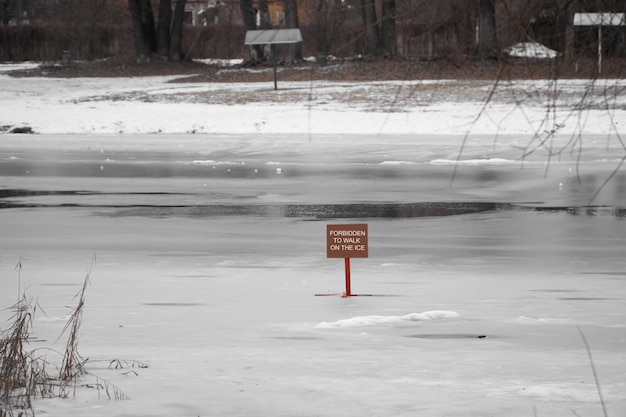 Red sign dangerously thin ice without inscription snowtime danger