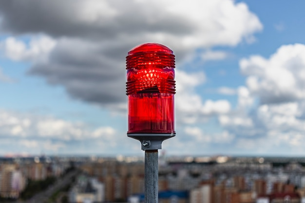 빨간 신호등. 도시 건물을 배경으로 다층 건물의 지붕에 있는 신호등. 항공 운송 보안.