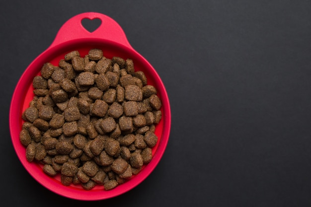 Red silicone bowl with dry dog food is on a dark . the  of the love of a pet