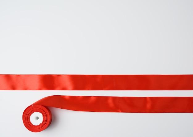 Red silk and bobbin on white, festive decor