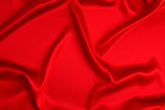 赤い絹またはサテンの高級生地の質感は、抽象的な背景として使用できます。上面図。