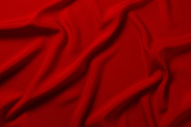 赤い絹またはサテンの豪華な生地のテクスチャは、抽象的な背景として使用できます。上面図