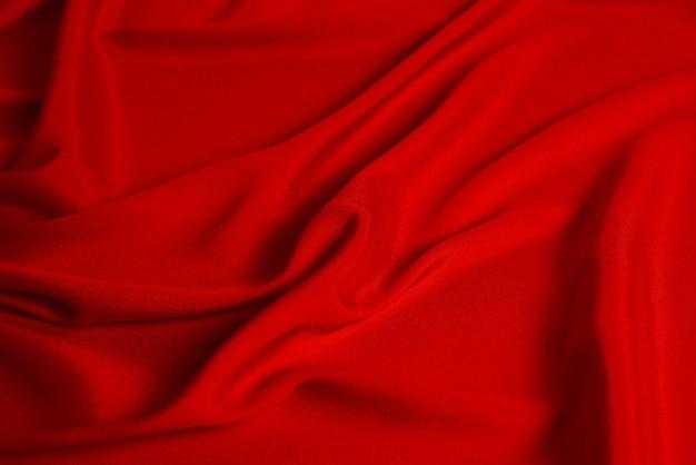 赤い絹またはサテンの豪華な生地のテクスチャは、抽象的な背景として使用できます。上面図。