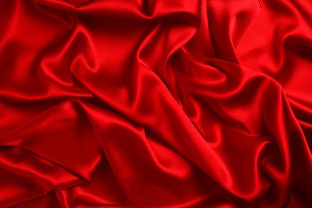 赤い絹またはサテンの高級生地の質感は抽象的な背景として使用できます