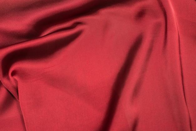 赤いシルクまたはサテンの豪華な生地のテクスチャーは、抽象的な壁として使用できます。上面図。