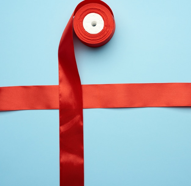 Red silk ribbon crossed on a blue background