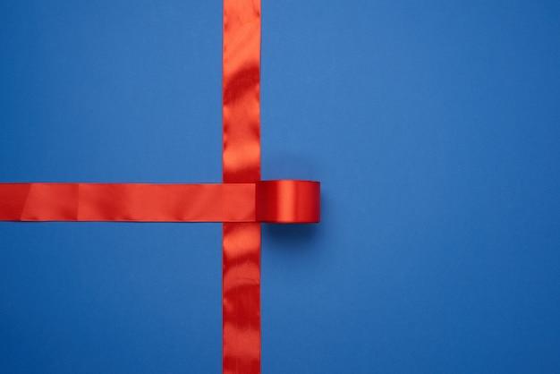 Red silk ribbon crossed on blue