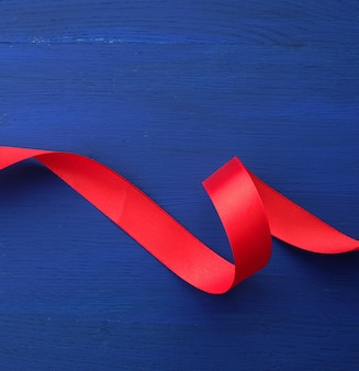 Red silk thin ribbon twisted on a blue wooden background