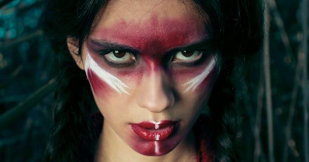 黄色い草でポーズをとって彼女の顔に赤い化粧をした赤い肌のインドの女の子